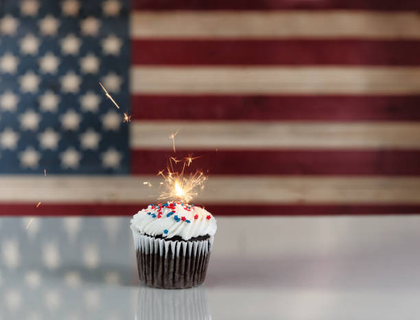 Glowing sparkler inside cupcake with rustic wooden flag of United States of America in background stock photo