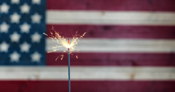 Glowing sparkler with rustic wooden flag of United States of America stock photo