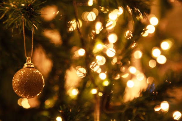 glowing sparkling gold defocused light illumination background with decorated christmas tree. happy holidays, festival design decoration. - happy holidays stock pictures, royalty-free photos & images