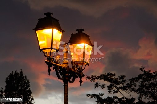 Vintage street lamp, slightly glowing with orange light in the rosy dusk, with trees silhouettes in the background