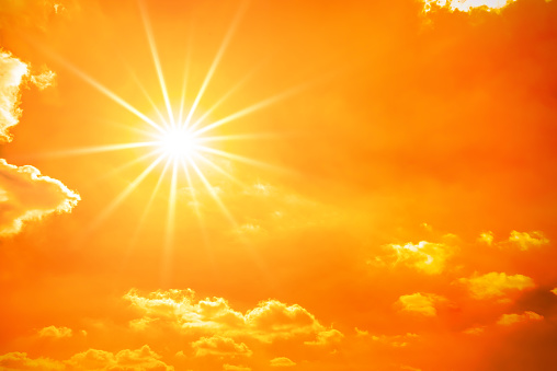 Hot summer or heat wave background, orange sky with clouds and glowing sun