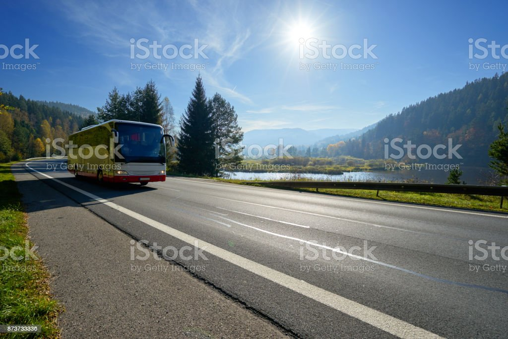Glowing sun over the landscape with a bus traveling on the road around a lake and forested mountains in autumn stock photo