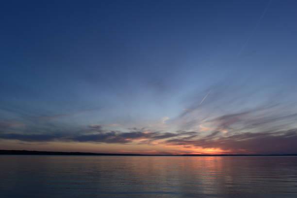 świecące światło słoneczne na bezchmurnym niebie zmierzchu w ciszy letniego wieczoru przed zmrokiem na jeziorze - zmrok zdjęcia i obrazy z banku zdjęć
