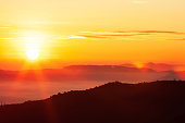Glowing sunrise shines over mountain range, magical star shape ray from the sun with lens flare. Exploration, inspiration concept.