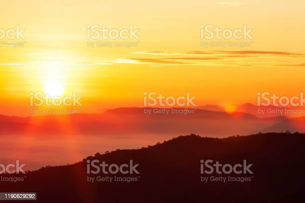 Photo of Glowing sunrise shines over mountain range.