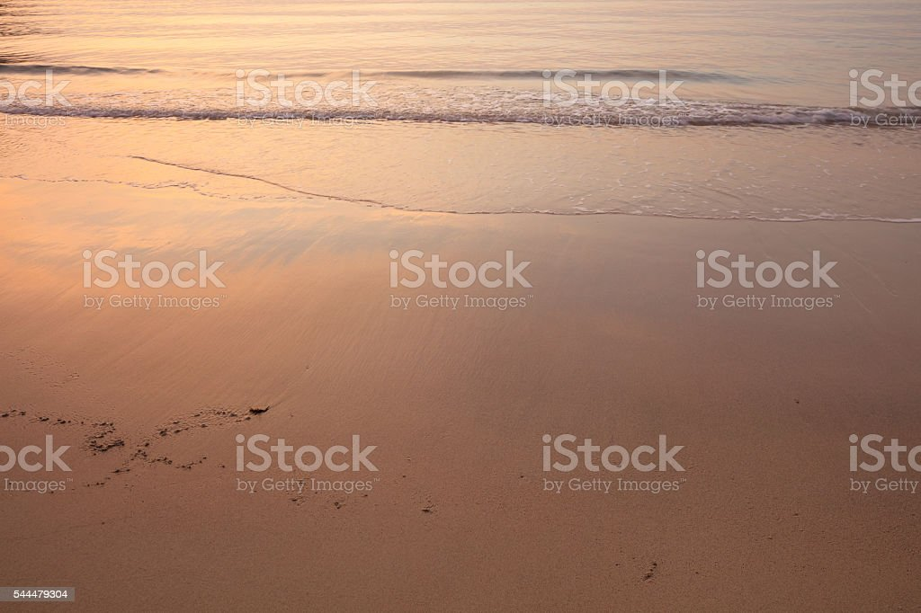Glowing sunset in ocean. Sky reflecting in water and sand stock photo