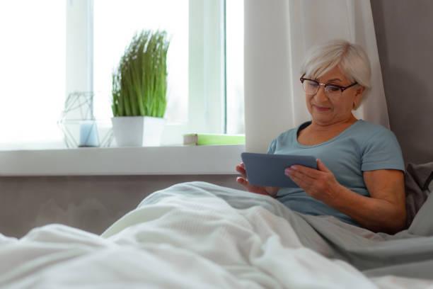 leuchtende frau in blauem t-shirt sehen film auf einem tablet - sexy granny stock-fotos und bilder