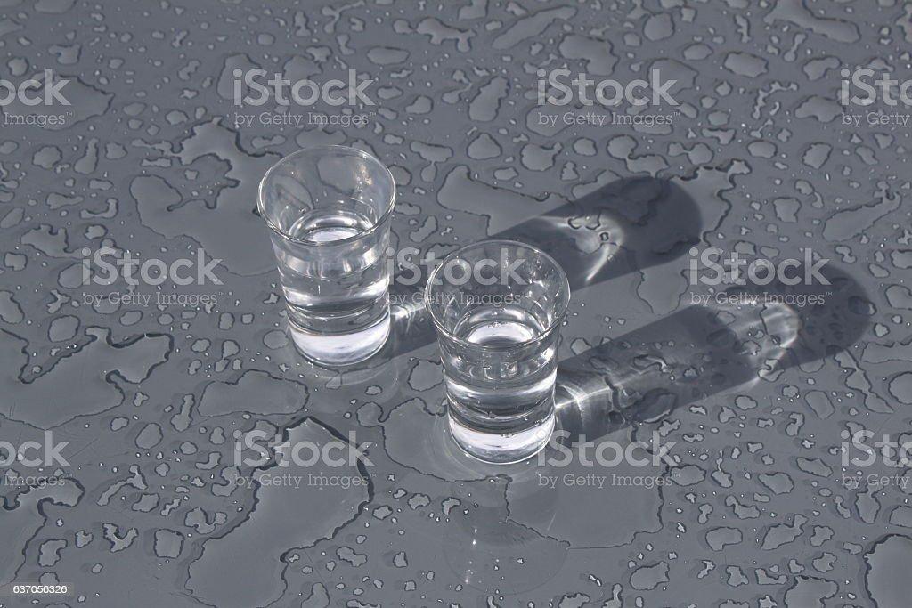 Gläser stehen auf nassem Tisch stock photo