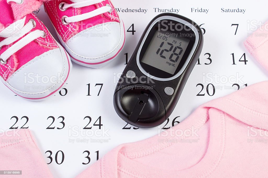 Glucometer and clothing for newborn, checking sugar level in pregnant stock photo
