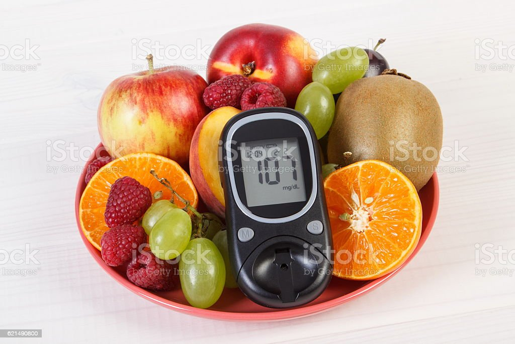 Glucometer and fresh fruits on plate, diabetes and healthy nutrition photo libre de droits