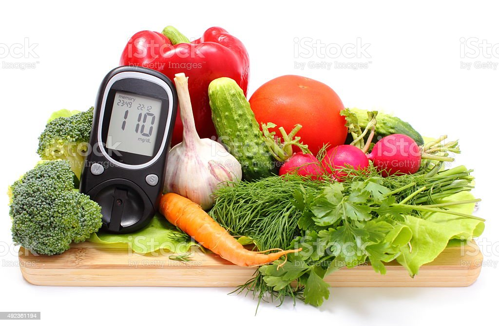 Glucometer and fresh vegetables on wooden cutting board stock photo