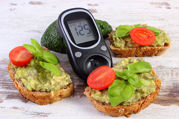 Glucometer and freshly sandwiches with paste of avocado, diabetes stock photo