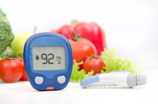 blutzuckermessgerät und lancelot auf gemüse-hintergrund - hypoglykämie stock-fotos und bilder