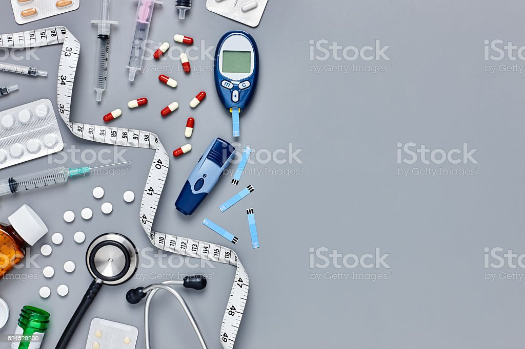 Glucometer and tape measure with medicines on gray background stock photo