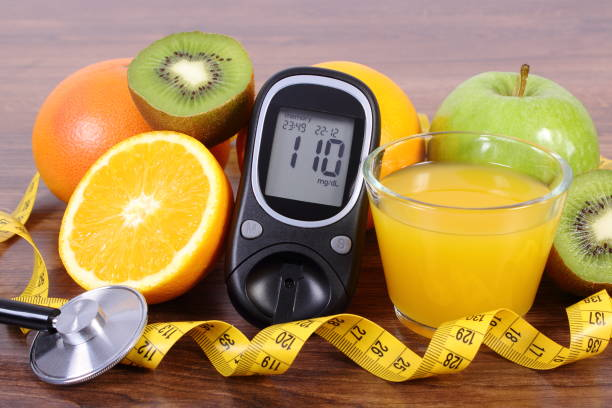 Glucometer for checking sugar level, stethoscope, fruits, juice and centimeter stock photo