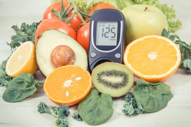 Glucometer zur Messung des Zuckerspiegels und reifer Früchte mit Gemüse als gesunder nährstoffreicher Snack mit Vitaminen – Foto