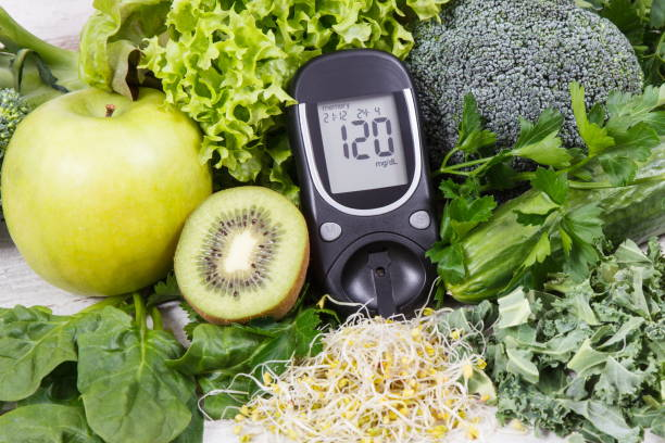 glucometer zur messung des zuckerspiegels, obst und gemüse mit sprossen als gesunde sinritious food bei diabetes - blutzuckermessung stock-fotos und bilder