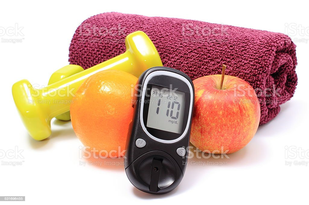 Glucometer, fresh fruits and dumbbells with purple towel stock photo