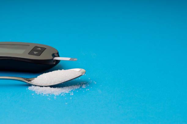 glucometer oder glukosemesser, zucker und löffel auf blauem hintergrund - hyperglycemia stock-fotos und bilder