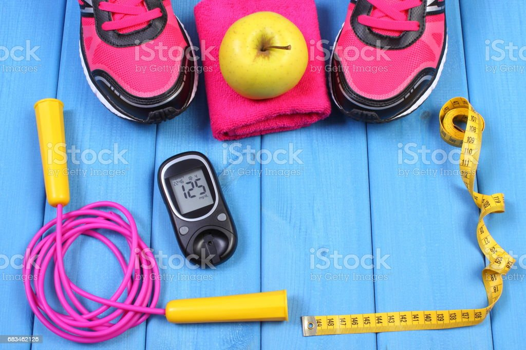 Glucometer, sport shoes, fresh apple and accessories for fitness on blue boards, copy space for text stock photo