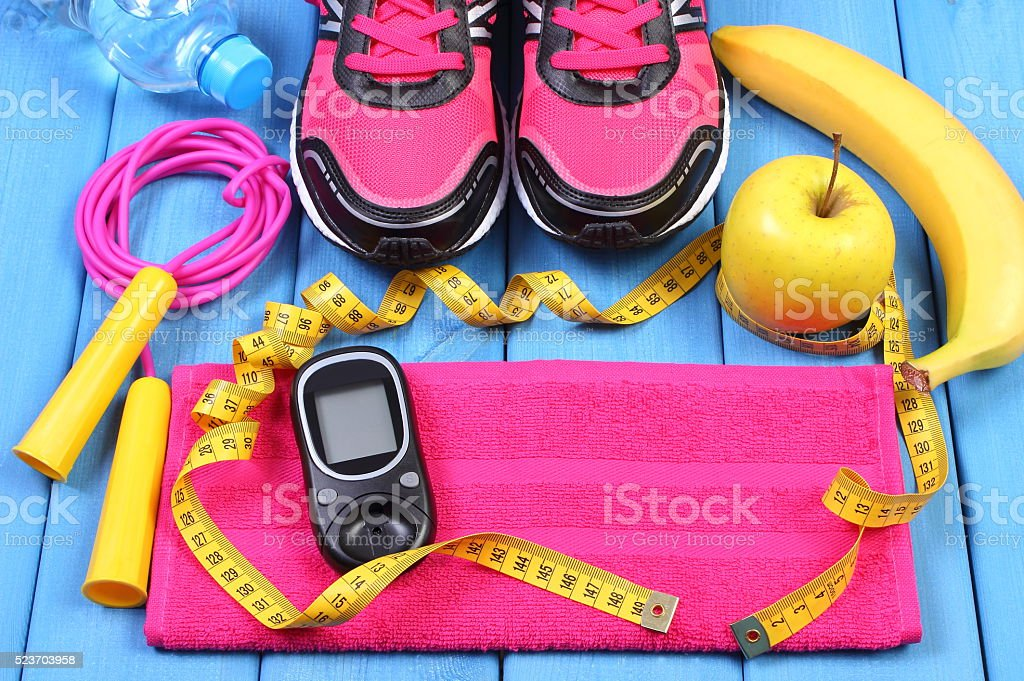 Glucometer, sport shoes, fresh fruits and accessories for fitness stock photo