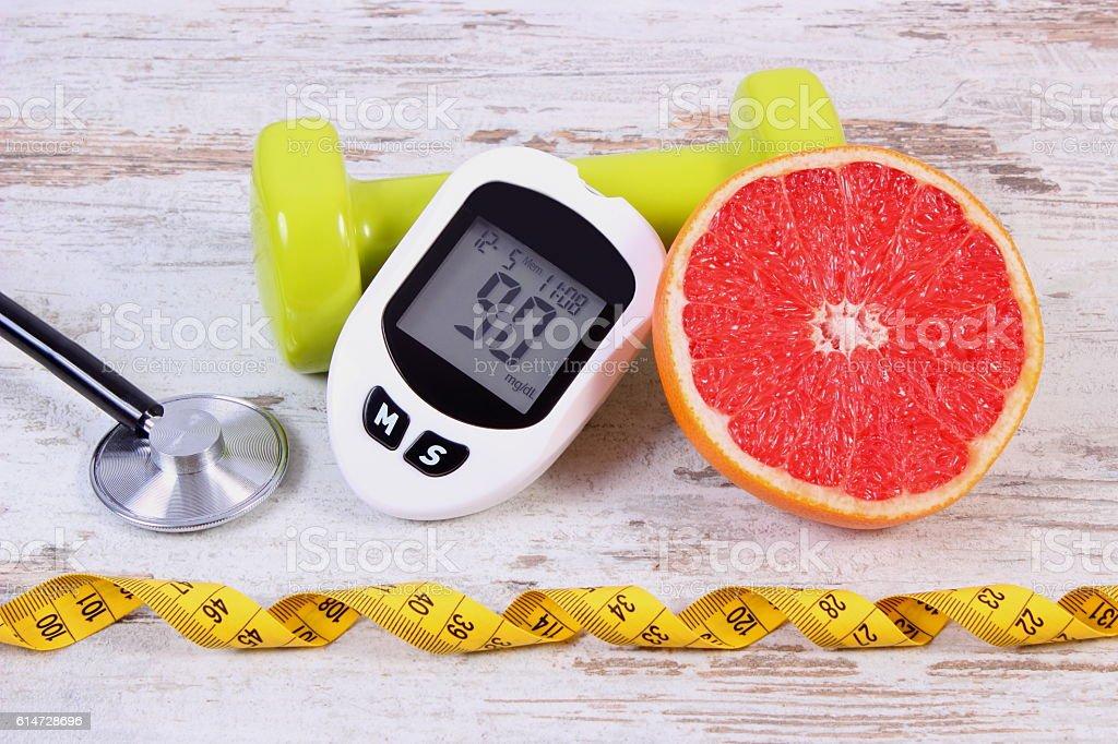 Glucometer, stethoscope, fresh grapefruit and dumbbells for fitness stock photo