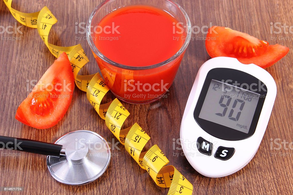 Glucometer with centimeter, fresh tomato and tomato juice, diabetes stock photo