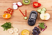 Glucose meter with clock made of fruits and vegetables containing vitamins showing time of 23 hours 55 minutes, concept of new years resolutions of healthy nutrition
