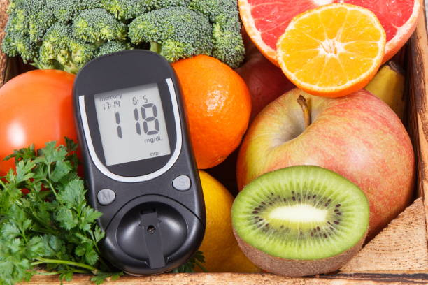 Glucometer with sugar level and natural fruits with vegetables. Diabetes and nutritious food containing minerals and vitamins stock photo