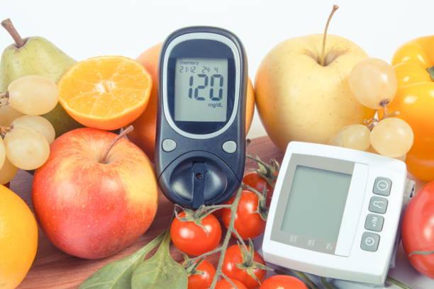 Glucometer mit Zuckerspiegel, Blutdruckmessgerät und Obst mit Gemüse, gesunder Lebensstil – Foto