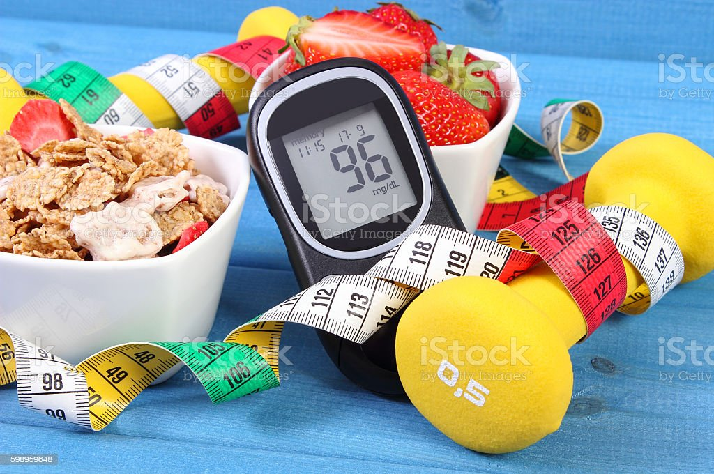 Glucometer with sugar level, healthy food, dumbbells and centimeter, diabetes stock photo