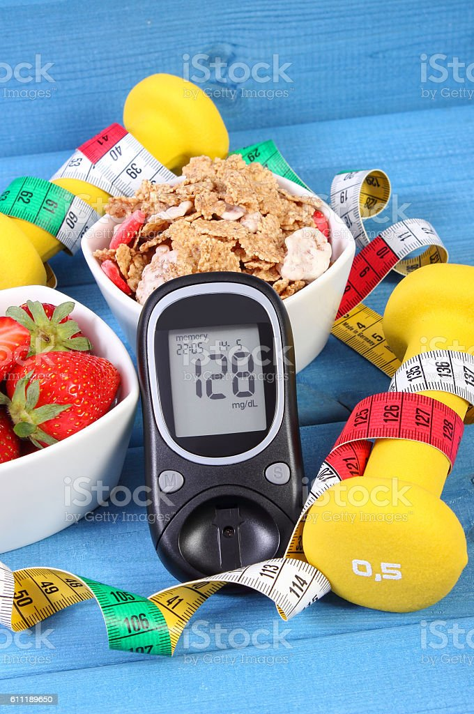 Glucometer with sugar level, healthy food, dumbbells and centimeter stock photo