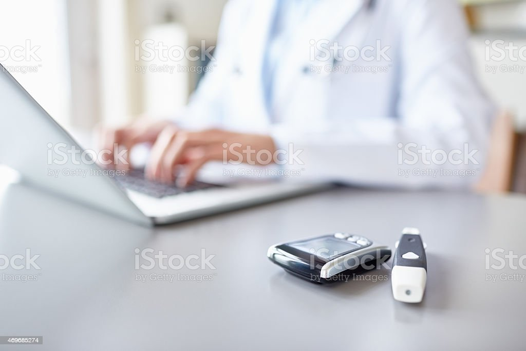Glucometers on desk with doctor using laptop in background stock photo