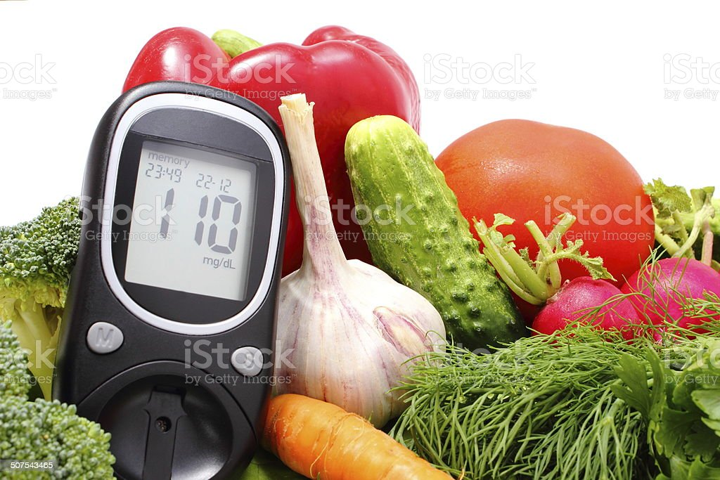 Glucose meter and fresh vegetables stock photo