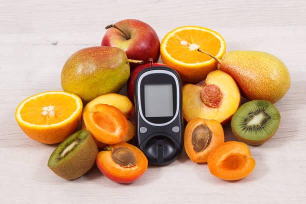 blutzuckermessgerät zur überprüfung zucker ebene und nahrhafte früchte als gesundes dessert für diabetiker - hyperglycemia stock-fotos und bilder