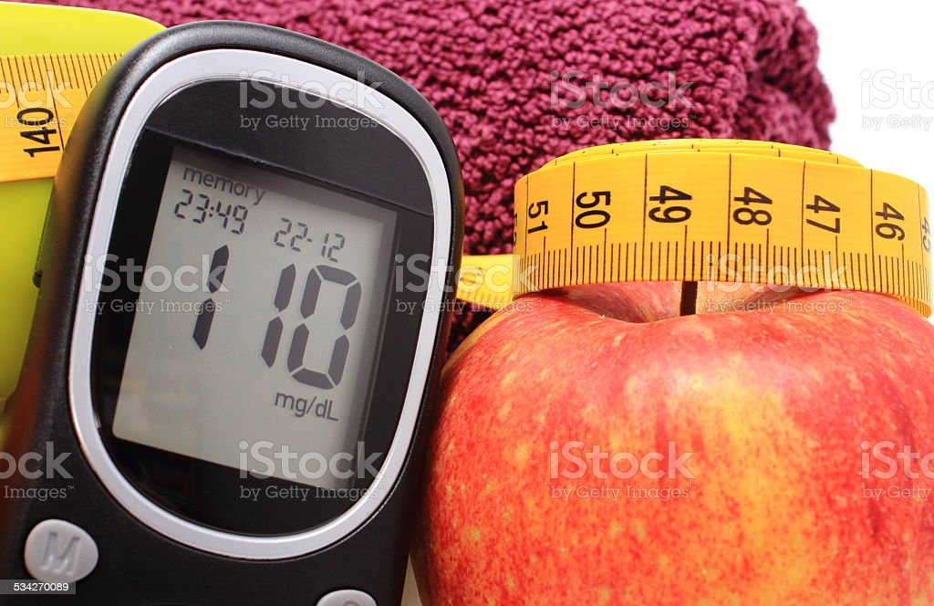 Glucose meter, fresh apple and tape measure stock photo