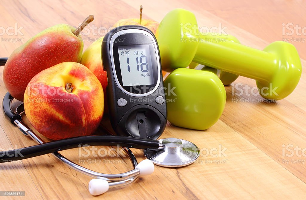 Glucose meter with medical stethoscope, fruits and dumbbells for fitness stock photo