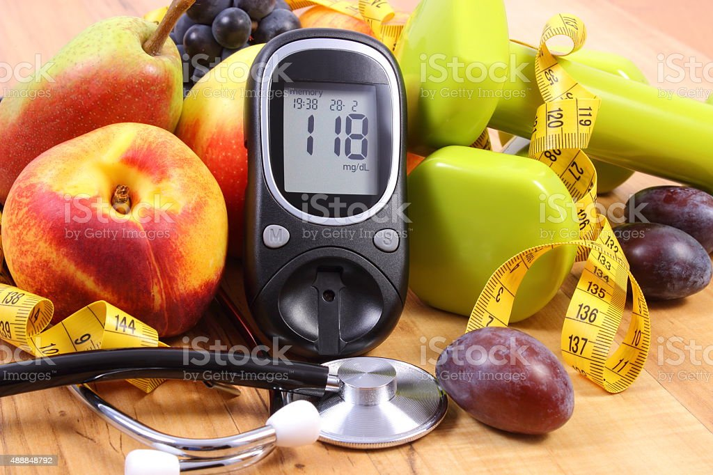 Glucose meter with medical stethoscope, fruits and dumbbells stock photo