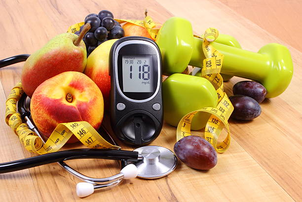glucose meter with medical stethoscope, fruits and dumbbells - diabetic stock photos and pictures