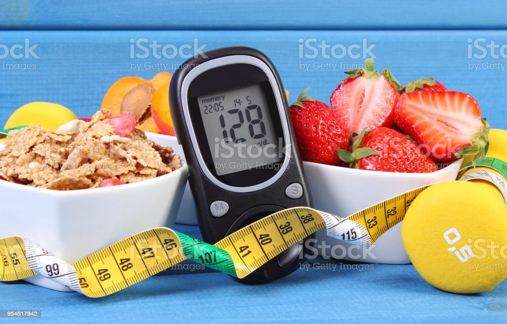 Glucose meter with sugar level, healthy food, dumbbells and centimeter, diabetes, healthy and sporty lifestyle stock photo