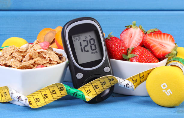 glucose meter with sugar level, healthy food, dumbbells and centimeter, diabetes, healthy and sporty lifestyle - diabetic stock photos and pictures