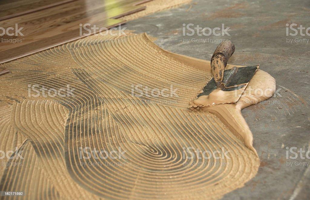 Glued down hardwood floor: Thinset mortar and trowel stock photo