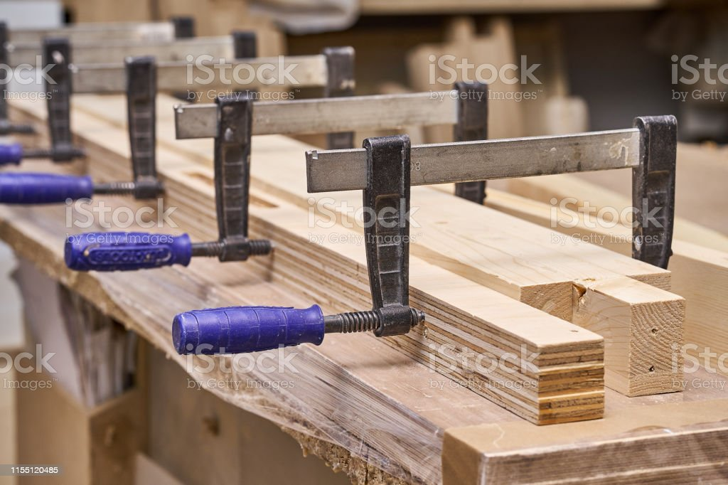 Gluing and clamping wooden detail in workshop. Furniture manufacture....