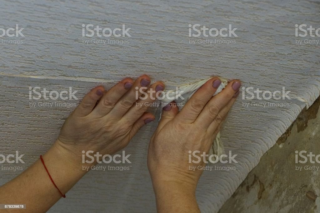 gluing of gray paper wallpaper with hands on the ceiling stock photo