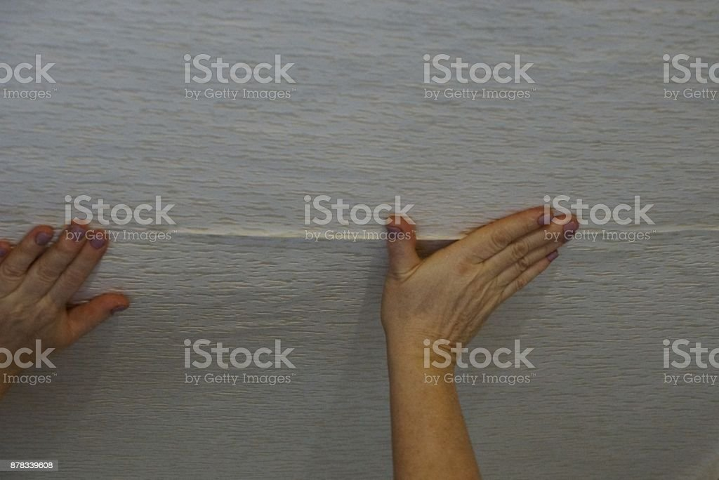 gluing paper wallpaper with hands on the ceiling stock photo