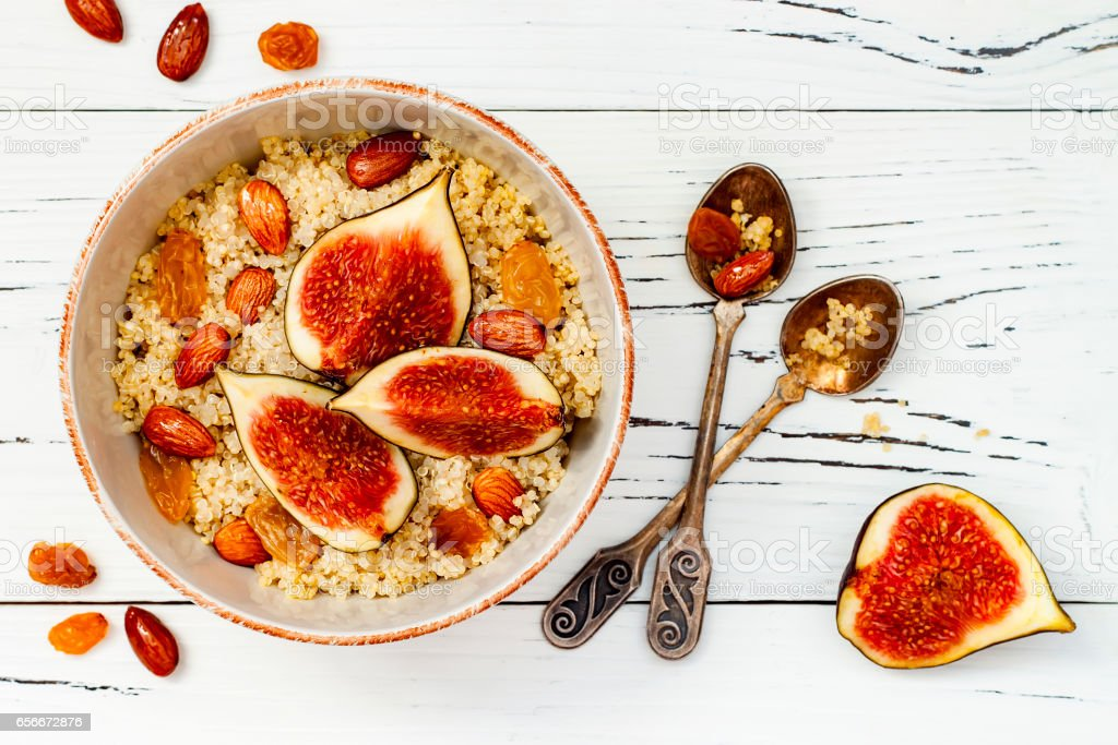 Gluten free amaranth and quinoa porridge breakfast bowl with figs, caramelized almonds, raisins and honey over rustic white table. Top view, overhead, flat lay. Copy space stock photo