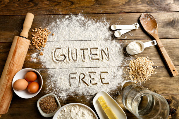 gluten free bread ingredients and utensils on wood frame background - food allergies stock photos and pictures