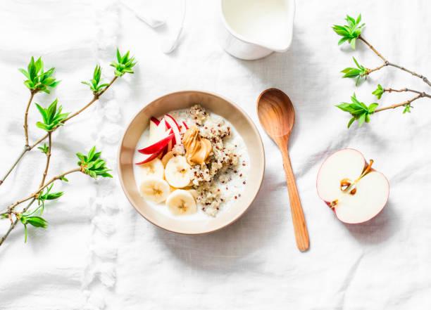 glutenfreies frühstück - quinoa, kokosmilch, banane, apfel, peanut butter schüssel auf hellem hintergrund, ansicht von oben. leckere ernährung, vegetarische frühstück oder snack. flach zu legen - getreidebrei stock-fotos und bilder