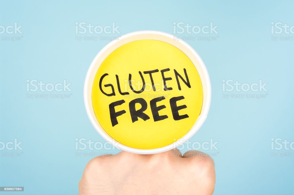 Gluten Free healthy lifestyle concept. Fist holding a paper cup with the words gluten free. stock photo