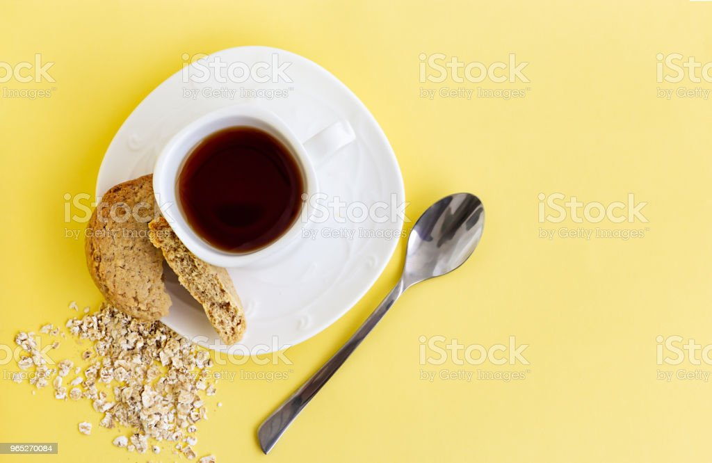Gluten free homemade oats oatmeal cookies and cup of tea or coffee espresso on pastel yellow background. Top view. Copy space. royalty-free stock photo